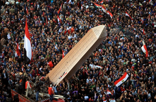 Egyptian protesters carry an obelisk with the names of those killed during last year's uprising, at a huge rally in Tahrir Square on January 25, 2012, marking the first anniversary of the uprising that toppled president Hosni Mubarak as a debate raged over whether the rally was a celebration or a second push for change. (Photo by Mahmud Hams/AFP Photo)