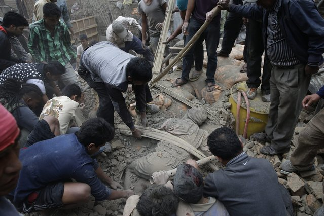 People try to free a man from the rubble of a destroyed building after an earthquake hit Nepal, in Kathmandu, Nepal, 25 April 2015. A 7.9-magnitude earthquake rocked Nepal destroying buildings in Kathmandu and surrounding areas, with unconfirmed rumours of casualties. (Photo by Narendra Shrestha/EPA)