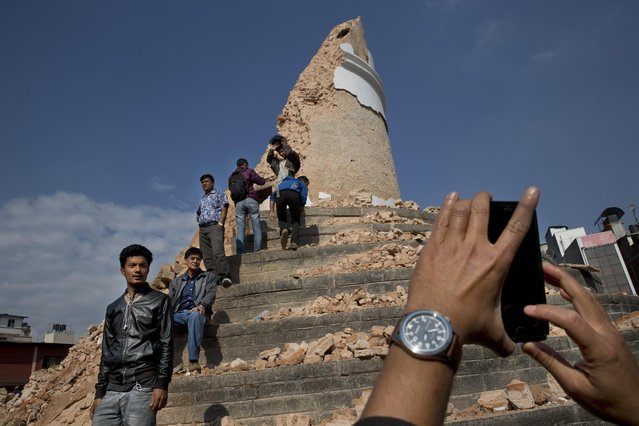 Locals take snapshots with their cell phones at the historic Dharahara Tower, a city landmark, that was damaged in Saturday's earthquake in Kathmandu, Nepal, Monday, April 27, 2015. (Photo by Bernat Armangue/AP Photo)