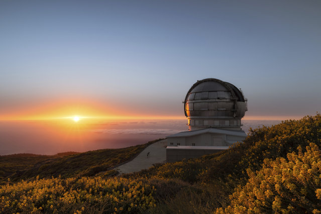 In this image released on Wednesday, July 11, 2018, the sun sets next to the Gran Telescopio Canarias at the Roque de los Muchachos Observatory on the island of La Palma in the Canaries, Spain. On July 27th Mars will be nearing the closest it's been to Earth in 15 years. This event, occurring in parallel to the longest lunar eclipse of the 21st century, creates a unique experience offered to six guests on Airbnb to visit the telescope and view the night sky from one of the best stargazing spots on the planet. (Photo by Antoni Cladera/Airbnb via AP Images)
