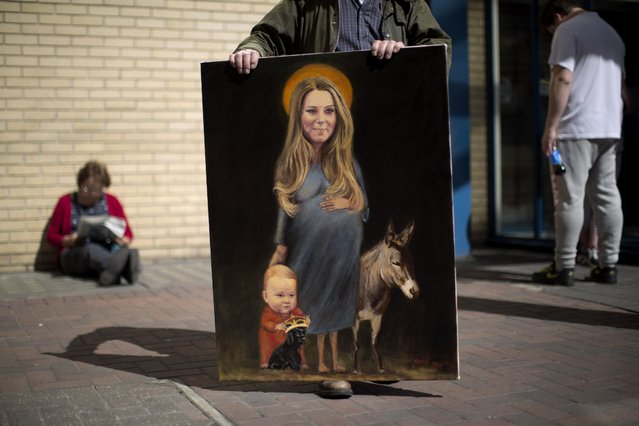 "Artist Kaya Mar poses for photographs with his painting entitled ""Saint Kate"" across the street from the Lindo Wing of St Mary's Hospital in London, Monday, April 27, 2015. Britain's Kate the Duchess of Cambridge is expected to give birth to her second child with her husband Prince William at the hospital in the coming days. Palace officials have said the baby is due in late April. A small number of dedicated royal fans are waiting or camping outside the hospital awaiting the imminent birth. (Photo by Matt Dunham/AP Photo)"