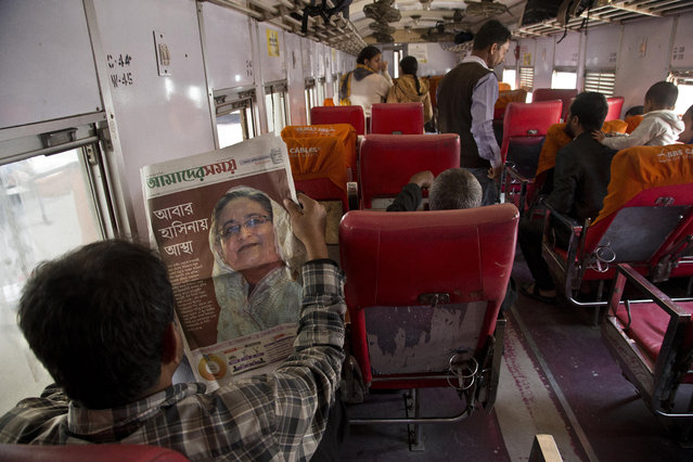 A Bangladeshi reads a newspaper showing a portrait of Prime Minister Sheikh Hasina a day after general elections, at a railway station in Dhaka, Bangladesh, Monday, December 31, 2018. Bangladesh's ruling alliance won virtually every parliamentary seat in the country's general election, according to official results released Monday, giving Hasina a third straight term despite allegations of intimidation and the opposition disputing the outcome. (Photo by Anupam Nath/AP Photo)