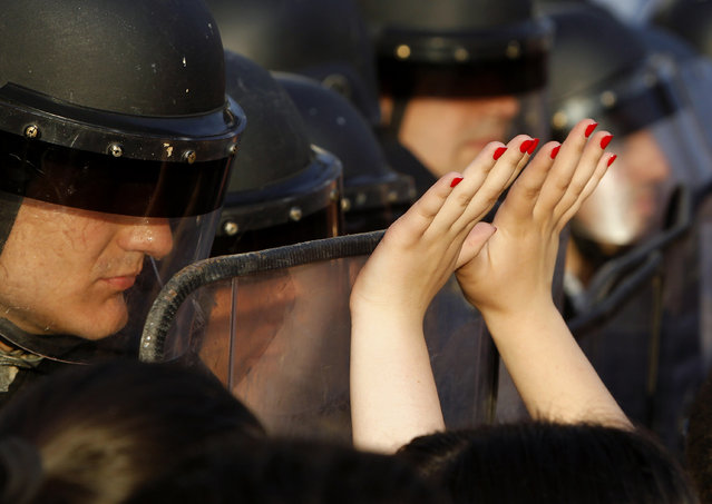 A woman lifts her hands up in front of the police during a protest in front of the Government building in Skopje Macedonia, on Tuesday, May 5, 2015. Macedonia's opposition leader has accused the country's prime minister of attempting to cover up the 2011 death of a 22-year-old who was beaten by police during post-election celebrations. (Photo by Boris Grdanoski/AP Photo)