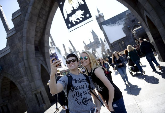 """Guests pose before they enter Hogsmeade Village during a soft opening and media tour of """"The Wizarding World of Harry Potter"""" theme park at the Universal Studios Hollywood in Los Angeles, California in this picture taken March 22, 2016. (Photo by Kevork Djansezian/Reuters)"""