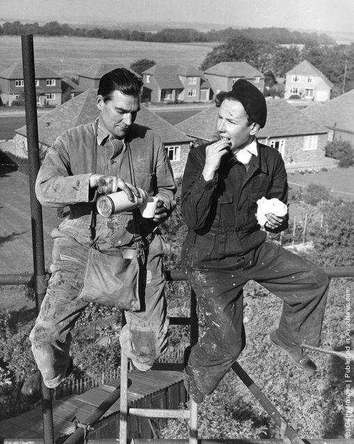 Builders Frank Agate, left, and Peter Stenning, enjoy their lunch high up on the scaffolding surrounding Moepham Windmill, at Moepham in Kent, which is being restored by Kent County Council