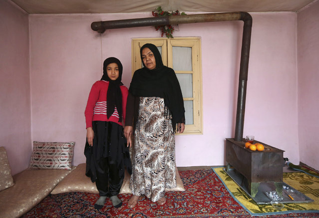 Noor Zia, 40, poses for a photograph with her daughter Saba Ahmadi, 11, at their home in Kabul February 13, 2014. Noor, who is a teacher, studied until she was 28. Her ambition was to become a doctor, but she couldn't afford the fees. She hopes her daughter will become a well-known, highly skilled doctor. Saba wants to go to university, and would like to become a renowned lawyer. (Photo by Omar Sobhani/Reuters)