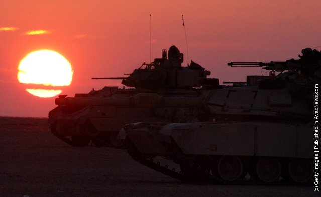 U.S. Army armor maneuvers at sunset near the Iraqi border in northern Kuwait