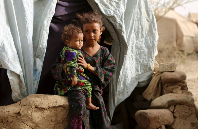 A girl holds her sister outside their family's hut at the Shawqaba camp for internally displaced people who were forced to leave their villages by the war in Yemen's northwestern province of Hajjah March 12, 2016. (Photo by Abduljabbar Zeyad/Reuters)