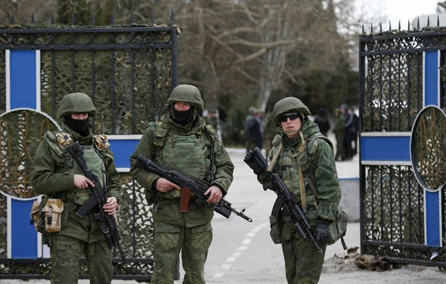 Armed men, believed to be Russian servicemen, stand guard outside the naval headquarters after it was taken over by pro-Russian forces in Sevastopol, March 19, 2014. (Photo by Vasily Fedosenko/Reuters)