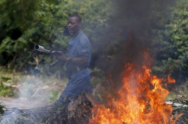 A policemen walks in front of a burned barricade after he fires a tear gas canisters at protesters during a protest against Burundi President Pierre Nkurunziza and his bid for a third term in Bujumbura, Burundi, May 21, 2015. (Photo by Goran Tomasevic/Reuters)