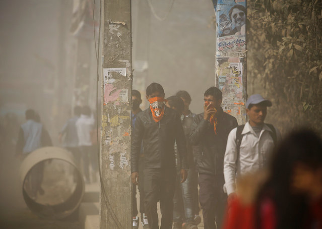 Pedestrians cover their faces as they walk along a dusty road in Kathmandu, Nepal February 27, 2017. (Photo by Navesh Chitrakar/Reuters)