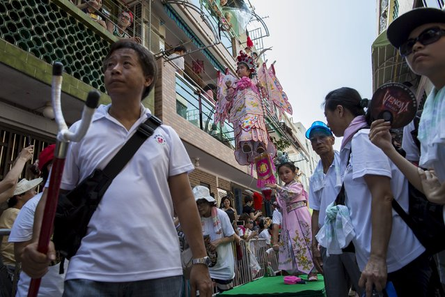A young girl, dressed in a traditional Chinese costume, stands above the crowd with the support of an elaborate rig of hidden metal rods as she takes part in a Bun Festival parade at Hong Kong's Cheung Chau island, China May 25, 2015. (Photo by Tyrone Siu/Reuters)