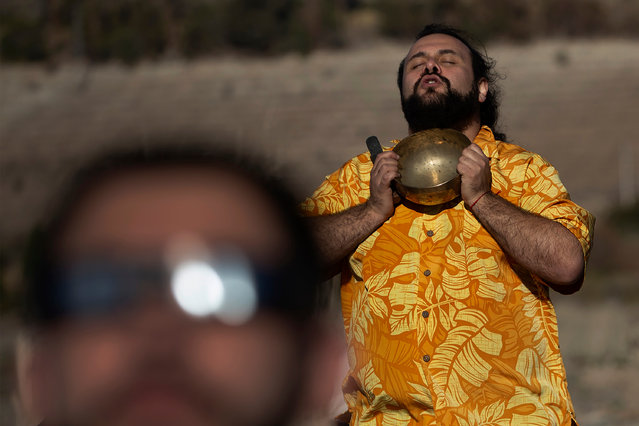 A man prays during the solar eclipse, from Puclaro, Coquimbo Region, Chile, on July 02, 2019. Tens of thousands of tourists braced Tuesday for a rare total solar eclipse that was expected to turn day into night along a large swath of Latin America's southern cone, including much of Chile and Argentina. (Photo by Claudio Reyes/AFP Photo)