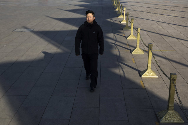 In this photo taken Wednesday, March 8, 2017, a participant arrives near the Great Hall of the People where a plenary session of the National People's Congress is held in Beijing, China. (Photo by Ng Han Guan/AP Photo)
