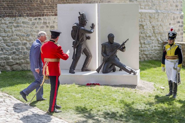 Britain's Prince Charles (L) walks by a newly-unveiled monument during a ceremony for the opening of the Hougoumont farm as part of the bicentennial celebrations for the Battle of Waterloo, near Waterloo, Belgium June 17, 2015. The commemorations for the 200th anniversary of the Battle of Waterloo will take place in Belgium on June 19 and 20. REUTERS/Geert Vanden Wijngaert/Pool