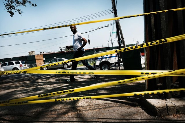 A man walks by police tape in the Brownsville neighborhood in Brooklyn where one person was shot and killed and 11 others were injured after two or more shooters opened fire during a massive block party on July 29, 2019 in New York City. Gunfire erupted during an annual community celebration, the Old Timers Event, which was being held at a playground and park. While crime has gone down in New York City overall, certain sections of Brooklyn have witnessed a spike in shootings and murders. Police are still looking for the shooters. (Photo by Spencer Platt/Getty Images)