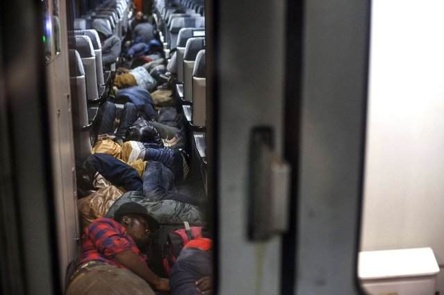 Migrants sleep on a train bound for the northern Serbian city of Subotica, near the border with Hungary, on June 28, 2015. Hungary on June 24 reversed its decision to suspend a key EU rule on processing asylum claims, a day after its announcement caused concern in Brussels and elsewhere. (Photo by Igor Pavicevic/AFP Photo)