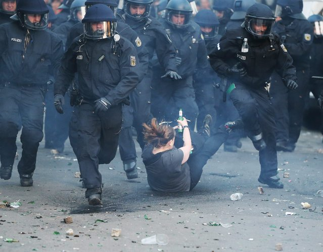 Riot police runs as a woman falls down during a May Day rally in the Kreuzberg district of Berlin, Germany, 01 May 2016. (Photo by Kay Nietfeld/EPA)
