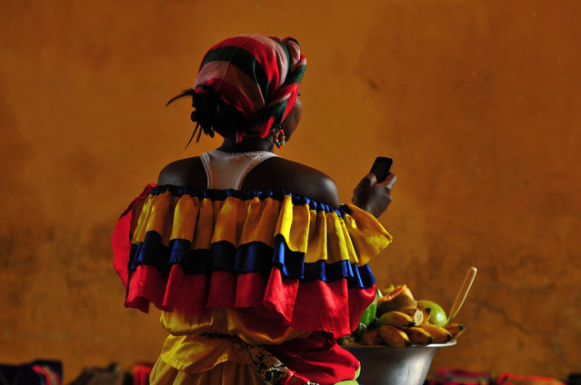 "Winner. ""I took this picture of a woman in traditional clothing in Cartagena, Colombia"". PAUL GOLDSTEIN, JUDGE: ""The blaze of colour from every angle, the boldness of the picture, taken from behind, which gives it so much more allure and frankly a superb get up. Did I mention the colours? Oh, and that looks suspiciously like a Nokia"". (Photo by Stanislav Shmelev/The Guardian)"
