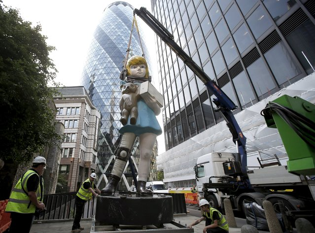 """Damien Hirst's statue, Charity (2002-2003), is installed opposite the Gherkin in London's Square Mile, Britain, July 4, 2015. The artwork is modelled on The Spastic's Society (now the charity Scope) collection boxes which were commonly found outside local chemists in the 1960s and 1970s, according to the artist's website. """"Charity"""" will be featured in Sculpture in the City, a yearly public art exhibition, which launches on July 9, 2015. (Photo by Peter Nicholls/Reuters)"""