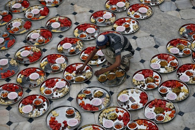 A Muslim man prepares plates of food for an Iftar (breaking of fast) meal inside a mosque during the holy month of Ramadan in Ahmedabad, India, July 5, 2015. (Photo by Amit Dave/Reuters)