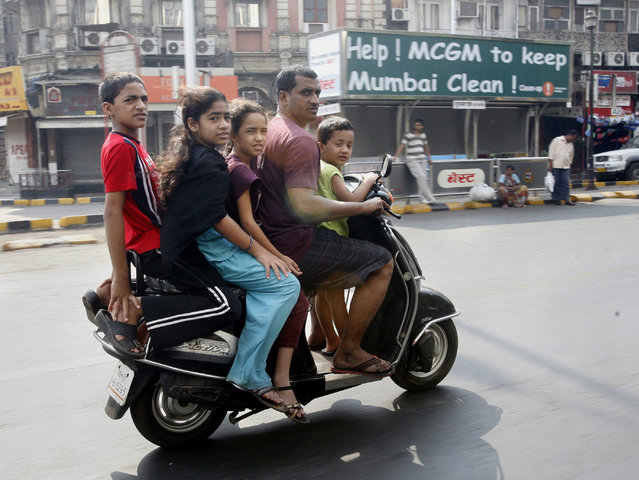 A man and children ride on a scooter in Mumbai April 5, 2009. (Photo by Arko Datta/Reuters)