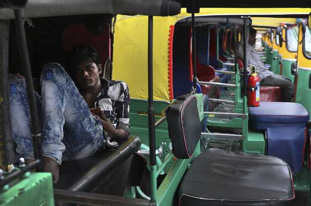 An auto-rickshaw driver rests during a public transport strike in New Delhi, India, Thursday, September 19, 2019. Commuters in the Indian capital are facing problems as a large section of the public transport, including private buses, auto-rickshaws and a section of app-based cabs Thursday remained off the roads in protest against a sharp increase in traffic fines imposed by the government under a new law. (Photo by Manish Swarup/AP Photo)