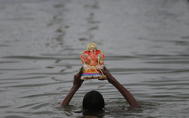 A devotee immerses an idol of the Hindu god Ganesh, the deity of prosperity, into a pond during the Ganesh Chaturthi festival in Ahmedabad, September 3, 2019. (Photo by Amit Dave/Reuters)