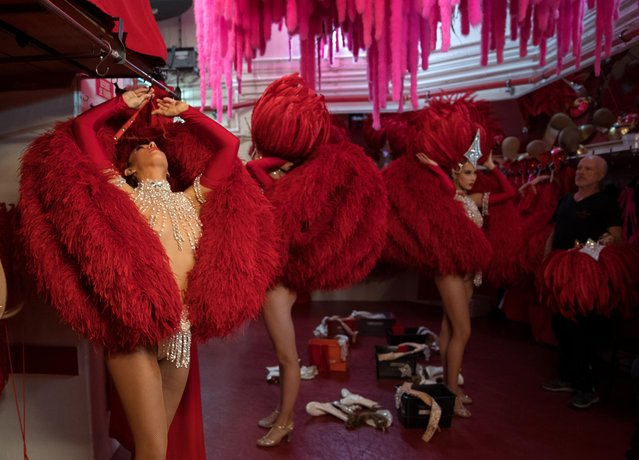 """Dancers get ready for the """"Red"""" set in the review """"Feerie"""" at the Moulin Rouge in Paris, France, July 3, 2018. For two performances every evening, 60 performers from 14 different countries twirl, kick and dance their way through the """"Feerie"""" show, the review that is now the mainstay of the Moulin Rouge's repertoire. But backstage – unseen by the 600,000 audience members who watch the show each year and quaff their way through nearly a quarter of a million bottles of champagne – is a different kind of choreography; the sophisticated machinery of costume changes and scenery-pulling needed to make the show happen. (Photo by Philippe Wojazer/Reuters)"""