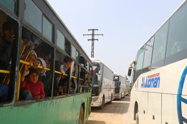 People who were evacuated from four besieged towns, as part of a reciprocal evacuation deal, travel to their respective destinations with one convoy (R) going to rebel-held Idlib and another convoy (L) to government-held Aleppo, as they wait at a transit point in al-Rashideen, Syria April 21, 2017. (Photo by Ammar Abdullah/Reuters)