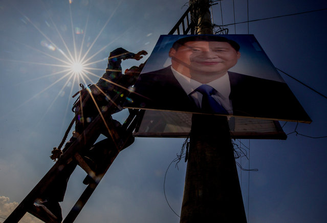 Nepalese government worker places a poster of Chinese president Xi Jinping on an electric pole in Kathmandu, Nepal, 11 October 2019. President of China Xi Jinping will make a two-day state visit to Nepal on 12 October, at the invitation of Nepalese President Bidya Devi Bhandari. (Photo by Narendra Shrestha/EPA/EFE)