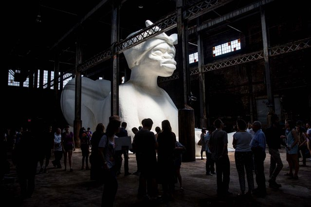"""People view Kara Walker's """"A Subtlety"""", a seventy-five and a half feet long and thirty-five and a half feet tall sphinx made in part of bleached sugar at the former Domino Sugar Refinery on May 10, 2014 in the Williamsburg neighborhood of the Brooklyn borough of New York City. The show opened today, is free to the public and will run until July 6th. (Photo by Andrew Burton/Getty Images)"""
