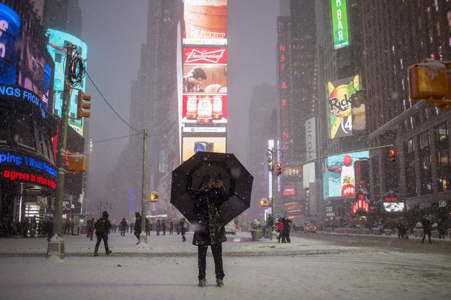 A man stands under an umbrella while photographing a snow storm in Times Square, New York, in this January 26, 2015 file photo. (Photo by Adrees Latif/Reuters)