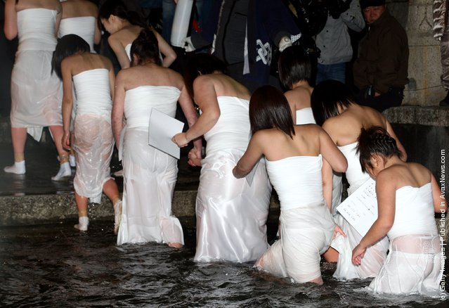 Japanese women emerge from freezing cold water during Saidaiji Naked Festival, at Saidaiji Temple