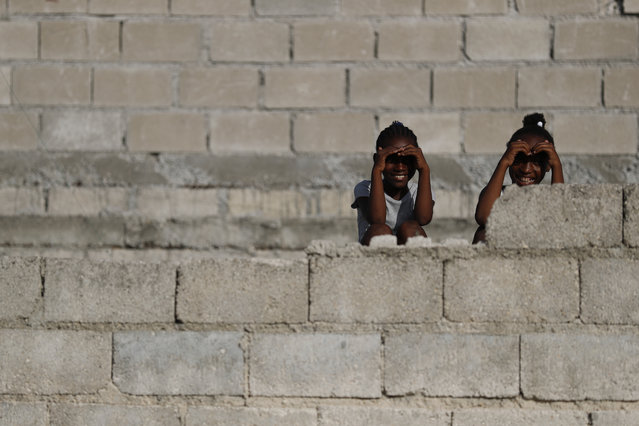Girls peer over a wall from one rooftop to another inside the Delmas neighborhood of Port-au-Prince, Haiti, Tuesday, October 8, 2019. With schools still shuttered and parents worried about a climate of insecurity as protests calling for the resignation of the president enter their fourth week, few children are visible on the capital's streets. (Photo by Rebecca Blackwell/AP Photo)