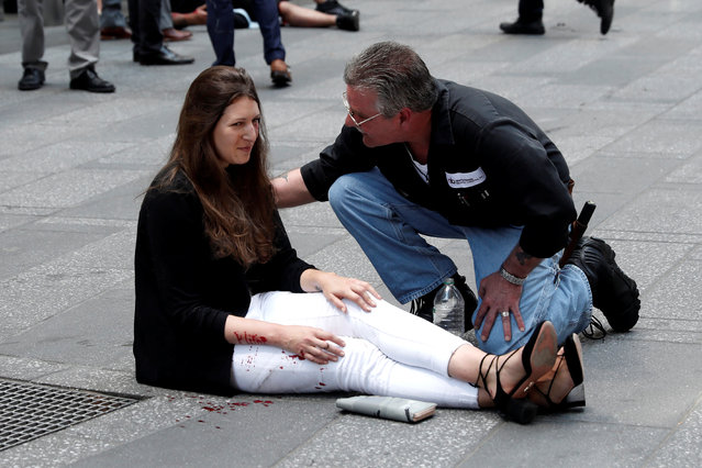 A man helps an injured woman on the sidewalk in Times Square after a speeding vehicle struck pedestrians on the sidewalk in New York City, May 18, 2017. (Photo by Mike Segar/Reuters)