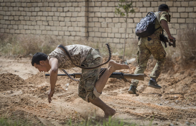 Fighters loyal to the internationally recognised Government of National Accord (GNA) run for cover during clashes with forces loyal to strongman Khalifa Haftar south of the capital Tripoli's suburb of Ain Zara, on April 25, 2019. (Photo by Fadel Senna/AFP Photo)