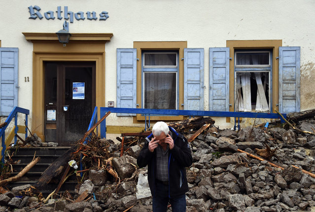 A man makes a phone call in front of an avalanche of debris that hit the town hall in Braunsbach, Germany, Monday, May 30, 2016. Authorities said three people are suspected to have died as floods struck Germany. Southern and western Germany, along with other parts of Europe, experienced heavy rainstorms over the weekend. (Photo by Marijan Murat/DPA via AP Photo)