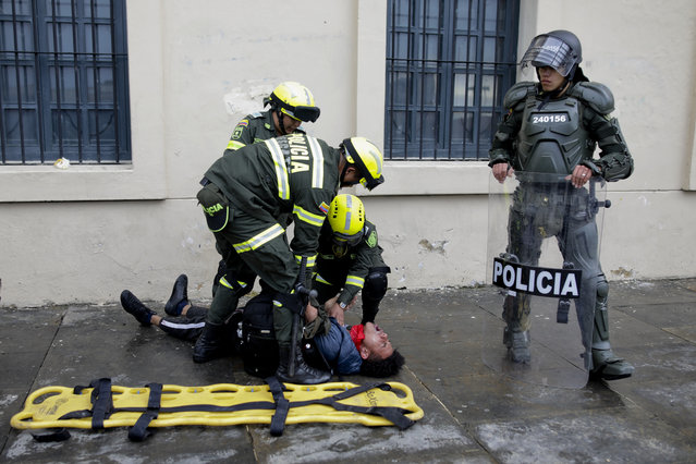 Police attend an anti-government protester affected by tear gas during clashes in downtown Bogota, Colombia, Friday, November 22, 2019. Labor unions and student leaders called on Colombians to bang pots and pans Friday evening in another act of protest while authorities announced three people had died in overnight clashes with police after demonstrations during a nationwide strike. (Photo by Ivan Valencia/AP Photo)