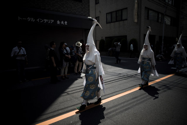 In this picture taken on May 19, 2017, heron- hooded dancers parade during the Sanja Matsuri festival in Tokyo. (Photo by Fred Dufour/AFP Photo)