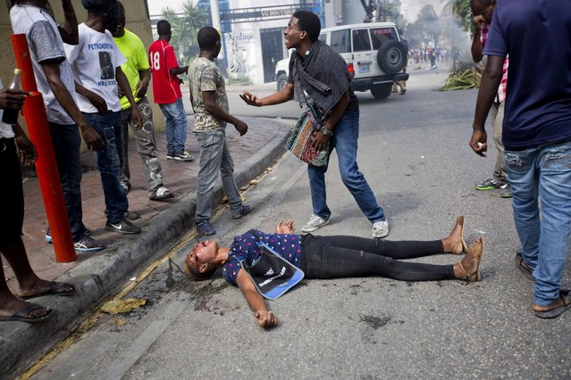 A demonstrator asks for help for a woman who was shot during clashes with national police officers, as they demanded the resignation of President Jovenel Moise and demanding to know how Petro Caribe funds have been used by the current and past administrations, in Port-au-Prince, Haiti, Thursday, February 7, 2019. Much of the financial support to help Haiti rebuild after the 2010 earthquake comes from Venezuela's Petro Caribe fund, a 2005 pact that gives suppliers below-market financing for oil and is under the control of the central government. (Photo by Dieu Nalio Chery/AP Photo)