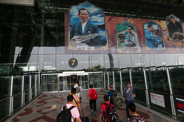 People are seen at Suvarnabhumi Airport, which is decorated with pictures of Thailand's King Bhumibol Adulyadej, in Bangkok, Thailand, April 2, 2016. (Photo by Jorge Silva/Reuters)