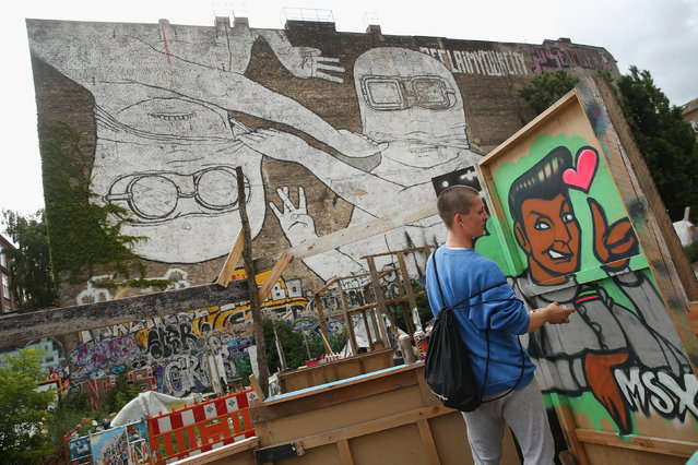 Dutch artist Ms. X works at her outdoor studio under a mural titled 'Brothers' by Blu and JR at the Cuvrystrasse squat in Kreuzberg district on June 26, 2014 in Berlin, Germany. Berlin, with its long tradition of counter-culture, has become a mecca for street art of all dimensions and messages. (Photo by Sean Gallup/Getty Images)