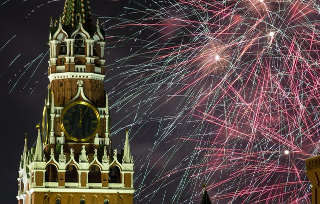 Fireworks explode over the Kremlin during New Year's celebrations in Red Square with the Spasskaya Tower in Moscow, Russia, Wednesday, January 1, 2020. Russians began the world's longest continuous New Year's Eve with fireworks and a message from President Vladimir Putin urging them to work together in the coming year. (Photo by Denis Tyrin/AP Photo)