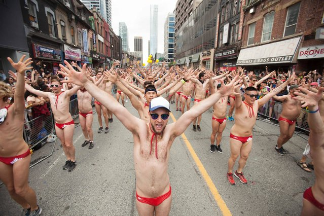 A group of men dance during the Pride Parade in Toronto, Ontario, June 25, 2017. (Photo by Geoff Robins/AFP Photo)