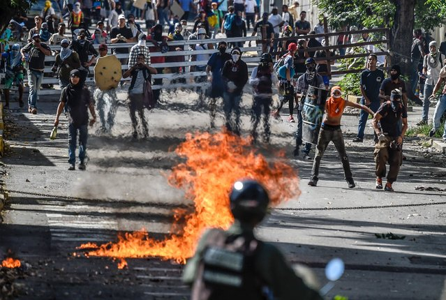 Opposition activists and riot police clash during an anti-government protest in Caracas on July 4, 2017. (Photo by Juan Barreto/AFP Photo)