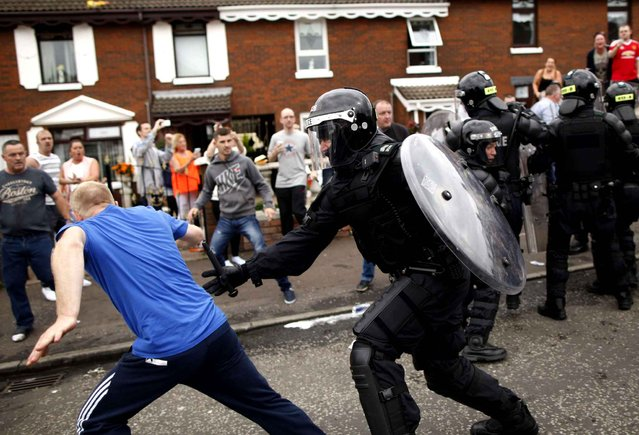 Riot police clear the streets in the Old Park area of north Belfast, Northern Ireland, Sunday, August 9, 2015. Minor trouble broke out in the area after a republican anti-internment rally was stopped by police from parading into the city centre. (Photo by Peter Morrison/AP Photo)
