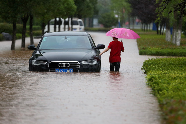 A resident walks past a car at a flooded area during heavy rain in Huangshan, Anhui Province, China, June 19, 2016. (Photo by Reuters/Stringer)