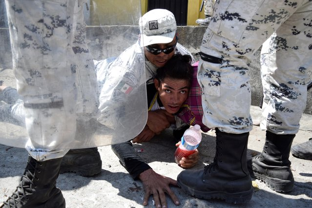 A member of Mexico's National Guard detains a migrant, part of a caravan travelling to the U.S., near the border between Guatemala and Mexico, in Ciudad Hidalgo, Mexico on January 20, 2020. (Photo by Jose Torres/Reuters)
