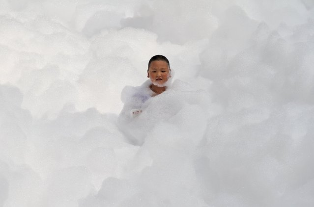 A boy is seen covered in foam, which is used to help participants cool off in the summer heat, during a running event in Yantai, Shandong province, China, July 25, 2015. (Photo by Reuters/Stringer)